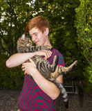 Teen boy and his tabby cat outside in the garden Stock Image