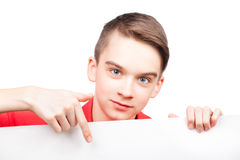 Teen boy holding banner pointing finger isolated on white. Cute teenager boy wearing red polo shirt  pointing his finger on blank white board or banner. Isolated Royalty Free Stock Image