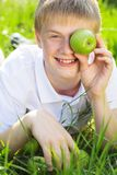 Teen boy is holding green apple near face Royalty Free Stock Images