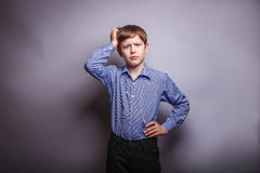 Teen boy holding his hand on head deep thought Stock Photo