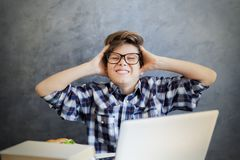 Teen boy holding his head and using laptop Royalty Free Stock Images