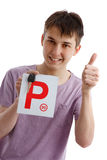 Teen boy holding P plates and car key. A happy male teen holds a red P plate and car key with thumbs up success sign.  White background Stock Images