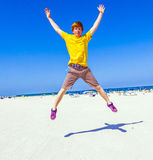 Teen boy jumping in the air at the beach Royalty Free Stock Photos
