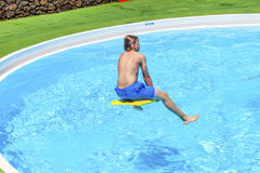 Teen boy jumping in the blue pool Royalty Free Stock Photo