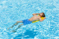 Teen boy jumping in the blue pool Stock Photo