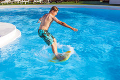 Teen boy  jumping in the blue pool Royalty Free Stock Photography