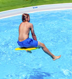 Teen boy jumping in the blue pool Royalty Free Stock Images