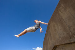 Teen Boy Jumping Blue Sky. Teen boy jumping off wall in blue sky on beach parkour Royalty Free Stock Photo
