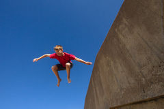 Teen Boy Jumping Blue Sky. Teen boy jumping off wall in blue sky on beach parkour Royalty Free Stock Photography