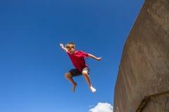 Teen Boy Jumping Blue Sky. Teen boy jumping off wall in blue sky on beach parkour Stock Image