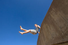 Teen Boy Jumping Blue Sky. Teen boy jumping off wall in blue sky on beach parkour Royalty Free Stock Images