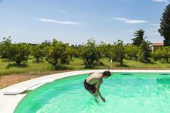 Teen boy jumping in pump in an outdoor pool. Between fields of crops in Sicily, Italy stock image