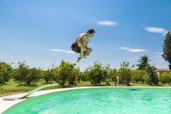 Teen boy jumping in pump in an outdoor pool. Between fields of crops in Sicily, Italy stock photography