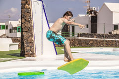 Teen boy jumps into the pool with his boogie board Royalty Free Stock Image