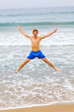 Teen boy jumps up the beach Stock Photography