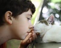Teen boy kiss cat sleeping on the car. Close up photo Royalty Free Stock Image