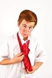 Teen boy knots his tie Stock Images