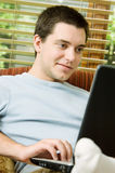 Teen boy on laptop. A teen boy at home looking at his laptop on the couch Stock Photo