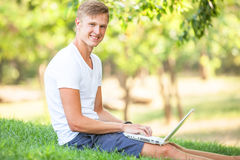 Teen boy with laptop Stock Images