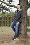 Teen boy leaning on tree outdoors Stock Photography