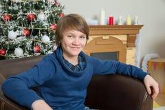 Teen boy in a leather armchair Stock Photos