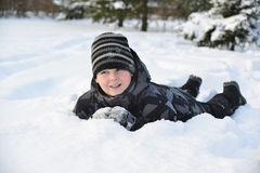 Teen boy lies on   snow in the winter forest Royalty Free Stock Images