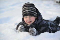Teen boy lies on   snow in the winter forest Royalty Free Stock Photography