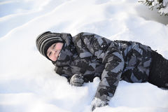 Teen boy lies on   snow in the winter forest Stock Photos