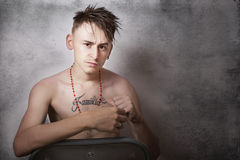 Teen boy looking aggressive and sitting on a chair Royalty Free Stock Images
