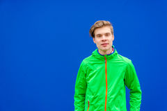 Teen boy looking into camera over contrast background outdoor. Teenager boy looking into camera posing over bright blue background contrasting with green jacket Stock Photo