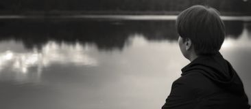 Teen boy looking to water in melancholy mood. Teen boy looking to water in melancholy sad mood, monochrome stock image