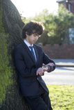 Teen boy looks at his watch. Teen boy in suit looks at his watch near the big tree. First date stock images