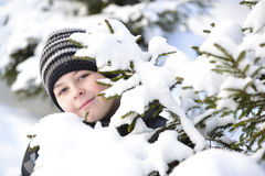 Teen boy looks out from behind trees in  winter forest Stock Images
