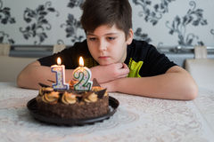 Teen boy looks thoughtfully at cake with candles on twelfth day of birth. Teen boy looks thoughtfully at a cake with candles on the twelfth day of birth Royalty Free Stock Images