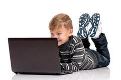 Teen boy lying on floor with laptop Stock Images