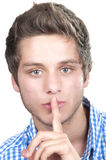 Teen boy making a quiet gesture Stock Photo