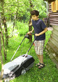 Teen boy moving grass lawn witm mover Stock Photo