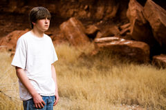 Teen boy in nature. Teen boy in Wyoming wilderness area, large red-brown boulders in background, copyspace royalty free stock images
