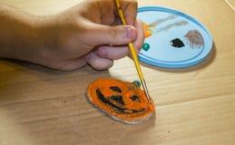 Teen Boy Painting Pumpkin Decoration Stock Image
