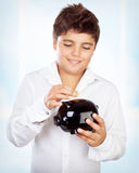 Teen boy with piggy bank Royalty Free Stock Photos