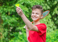 Teen boy playing badminton in park. Young teen boy playing badminton in meadow with forest in background. Child with badminton rackets in hand. Kid have fun in Stock Photo