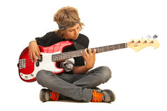 Teen boy playing bass quitar. Teen boy sitting on floor with legs crossed and playing bass guitar isolated on white background Stock Photo