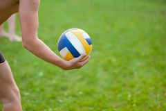 Teen boy playing beach volleyball. Volleyball player on the grass playing with the ball, a volleyball ball in his hand stock photos