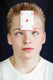 Teen Boy with Playing Card Stuck to Forehead royalty free stock image