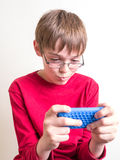 Teen Boy Playing with Cell Phone. A middle school boy texting his girlfriend or playing a video game on his cell phone or portable music MP3 player Stock Images