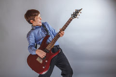 Teen boy playing guitar on gray background Stock Images