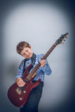 Teen boy playing  guitar on gray  background cross Royalty Free Stock Photo