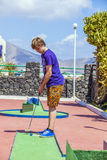 Teen boy plays minigolf. Smiling teen boy plays minigolf Royalty Free Stock Photos