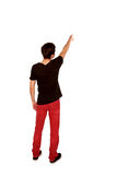 Teen boy pointing at something. Rear view. Royalty Free Stock Image