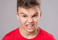 Teen boy portrait. Emotional portrait of irritated shouting teen boy. Furious teenager screaming and looking with anger at camera. Handsome outraged child Stock Photography